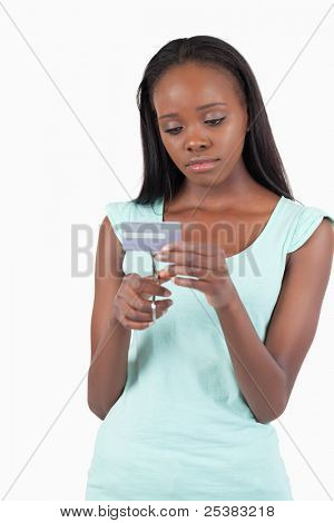 Sad woman destroying her credit card against a white background