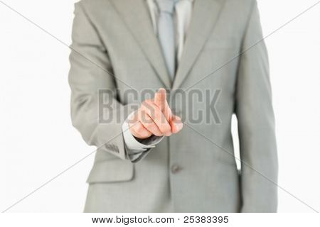 Businessman's finger activating futuristic touchscreen against a white background