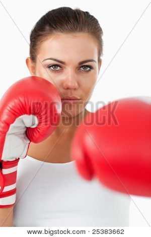 Female boxer hitting with her left against a white background