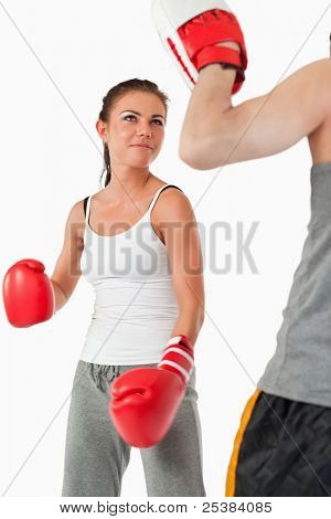 Young female in martial arts training against a white background