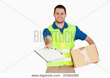 Smiling young delivery man with parcel asking for signature against a white background