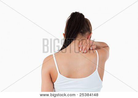 Back view of woman with pain in her neck against a white background