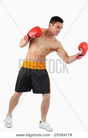 Side view of boxer performing uppercut against a white background