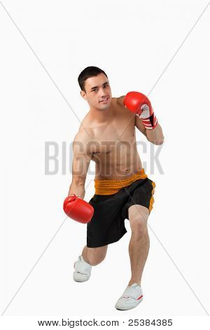 Young boxer starting to perform uppercut against a white background