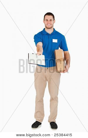 Smiling young salesman with parcel asking for signature against a white background