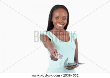 Smiling young woman using her credit card to pay against a white background