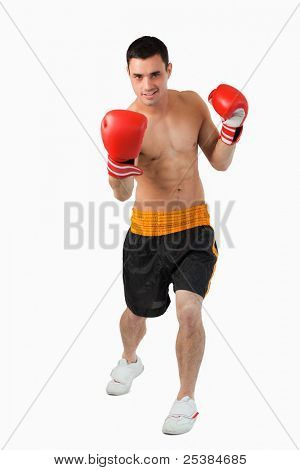 Young boxer performing uppercut against a white background