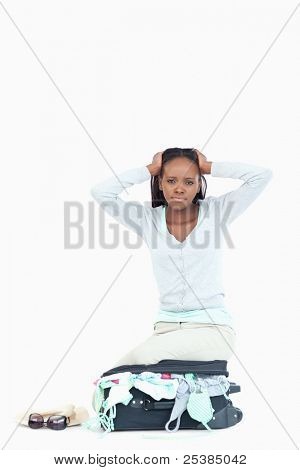 Suitcase of young woman is too full against a white background