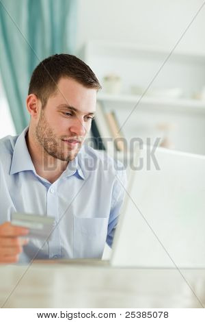 Young businessman with credit card and laptop in his home office