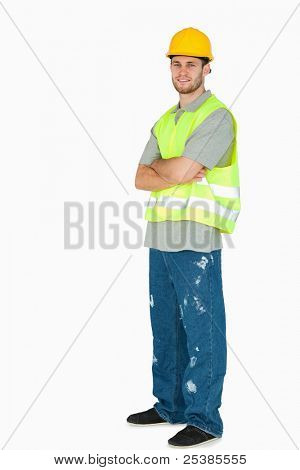 Side view of smiling young construction worker with arms folded against a white background