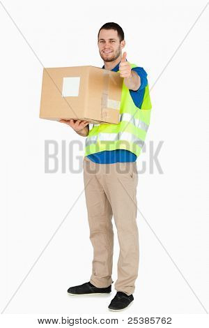 Smiling young delivery man giving thumb up white holding parcel against a white background