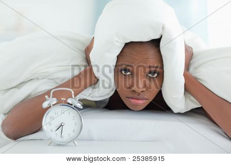 Exhausted woman covering her ears with a duvet while her alarm clock is ringing