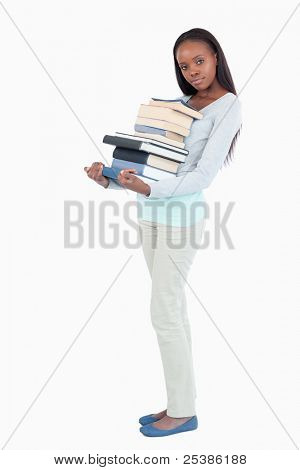 Side view of young woman with a pile of books against a white background
