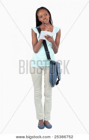 Joven estudiante con el pensamiento de la libreta de apuntes sobre fondo blanco