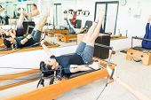 Active Fit Young Man Doing Exercise On Pilates Reformer In Health Club poster