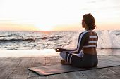 Image of strong young fitness woman outdoors in the beach make yoga meditate exercises. poster
