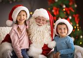 Little Children Sitting On Authentic Santa Claus Knees Indoors poster