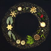 Christmas wreath garland with gold glitter, bauble decorations and winter flora on black background. poster