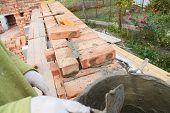 Bricklayer Worker Installing Red Blocks And Caulking Brick Masonry Joints Exterior Brick House  Wall poster