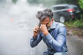 Mature Man Making A Phone Call After A Car Accident, Smoke In The Background. poster