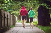 healthy jogging couple running in city park, runners team on morning training poster