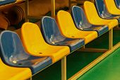 Multicolored Empty Plastic Chairs In The Stands Of The Stadium. Many Empty Seats For Spectators In T poster