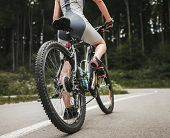 Young Woman Riding On Mountain Bicycle On Forest Road. Bike On Road. Biker Competition. Recreation A poster