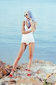 Fashionable Woman Posing In White Vintage Swimwear, Sunglasses And Silk Scarf On Rocky Beach poster