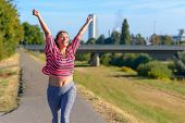 Happy Fit Young Woman Cheering And Celebrating As She Walks Along A River After Working Out Jogging poster