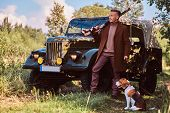 Hunter In Elegant Clothes Holds A Shotgun And Standing Together With His Beagle Dog Near A Retro Mil poster