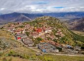 Tibetan Ganden Buddhist Monastery Lies In A Hilly Natural Amphitheater Mountains And Dramatic Views  poster