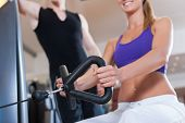 Young couple exercising in gym on different power machines to strengthen the muscles; the man is per