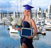 Graduate Student In Academic Dress And Cap With Flowers And Diploma After Graduation Ceremony. Kitci poster