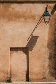 Orange Color Of The Weathered Wall With A Traditional Lantern Painted Dark Green And With Its Shadow poster