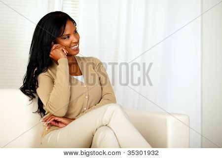 Young Woman Sitting On Sofa Talking On Cellphone