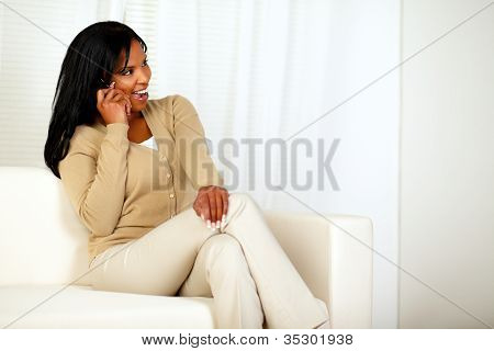 Pretty Woman Sitting On Couch Talking On Cellphone