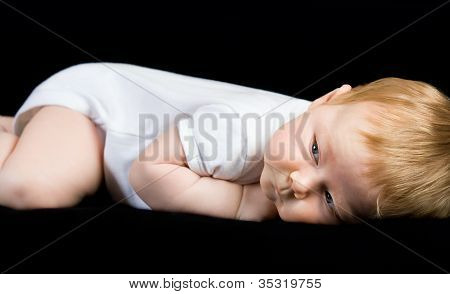 Happy The Child Is Lying On Its Side And Looks Toward