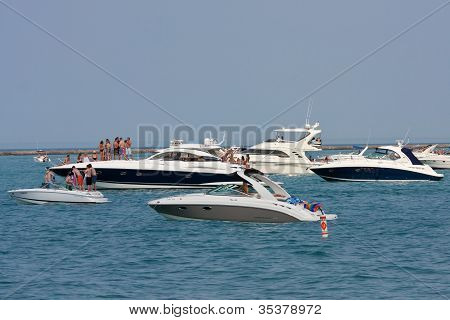 People Party On Boats Anchored On Lake Michigan In Chicago