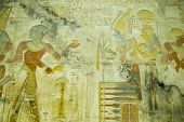 image of isis  - Ancient Egyptian bas relief carving showing the Pharaoh Seti I making an offering of incense to the god of the underworld Osiris with his wife, the goddess Isis standing behind.  