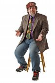 stock photo of newsboy  - Man with large build sits on stool dressed casually in tweed cap jacket and jeans - JPG