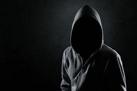 image of hooligan  - Silhouette of hooded man or hooligan over dark - JPG