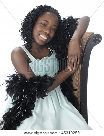 A happy preteen sitting in her soft green dress with a feathery black boa draped over her arms.  On a white background.