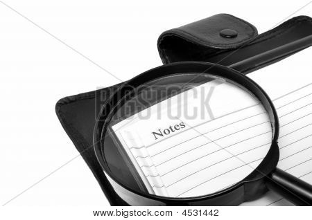 A Magnifying Glass And A Notepad