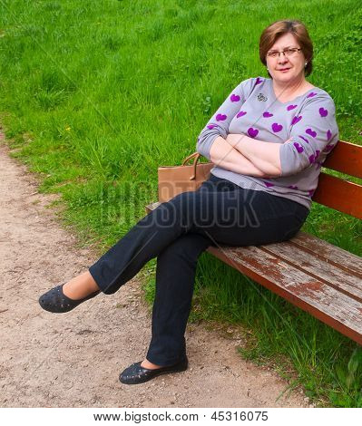 Middle-aged Woman Relaxing  On A Park Bench