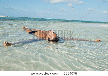 Man floating in water on the beach
