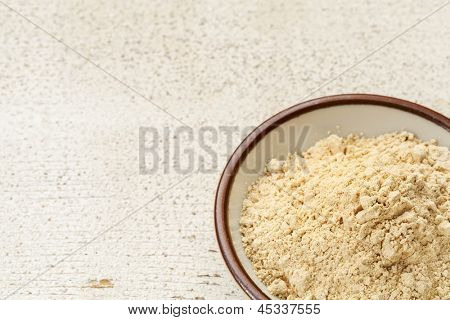 maca root powder (nutrition supplement - superfood from Andies) in a small ceramic bowl on a rustic barn wood