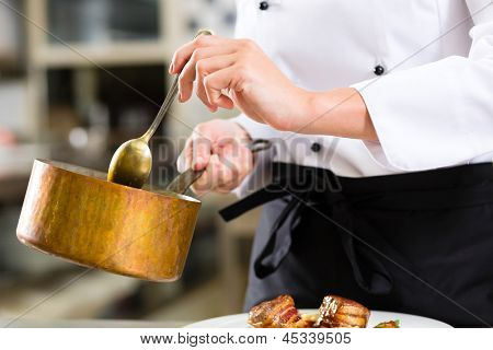 Female Chef in hotel or restaurant kitchen cooking, only hands to be seen, she is working on the sauce as saucier