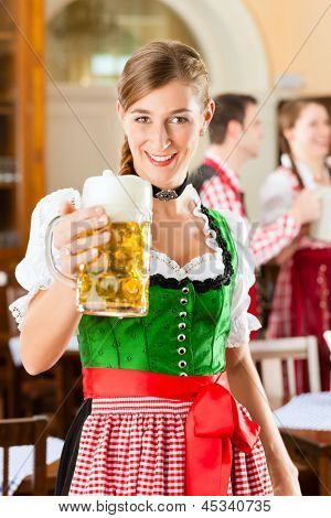 Young people in traditional Bavarian Tracht in restaurant or pub, one woman is standing with beer stein in front, the group in the background