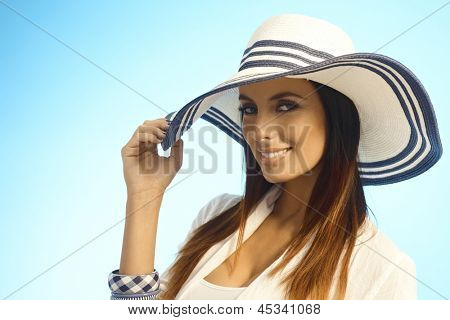 Closeup portrait of elegant attractive woman in straw hat, looking at camera, smiling happy.