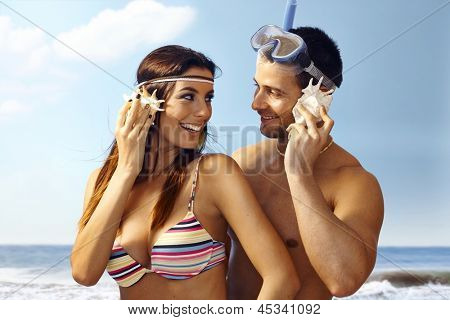 Happy loving couple on beach listening to murmur of sea in seashell, smiling.